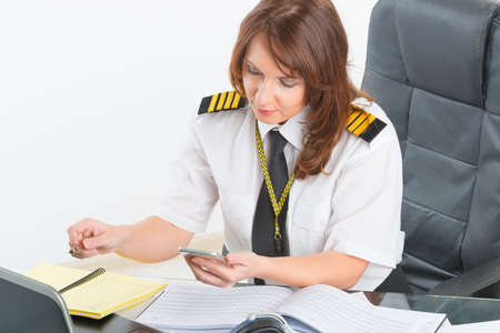 aircrew: Beautiful woman pilot wearing uniform with epaulettes using mobile phone and laptop at preflight briefing