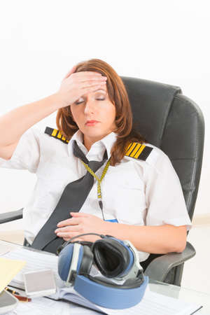 epaulettes: Overworked tired woman pilot wearing uniform with epaulettes resting or sleeping in briefing room Stock Photo