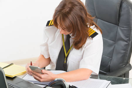 epaulettes: Beautiful woman pilot wearing uniform with epaulettes using mobile phone and laptop at preflight briefing
