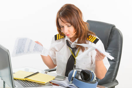 cpl: Overworked woman pilot wearing uniform with epaulettes holding papers in briefing room