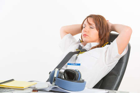 cpl: Overworked woman pilot wearing uniform with epaulettes resting or sleeping in briefing room Stock Photo