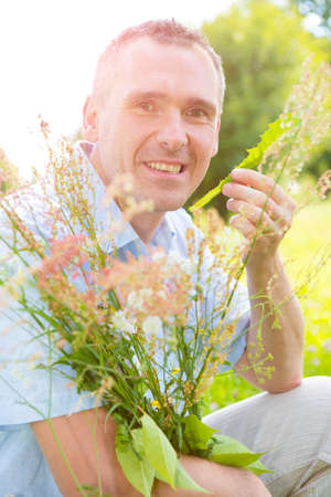 herbolaria: Hombre herbolario recogiendo hierbas silvestres Foto de archivo