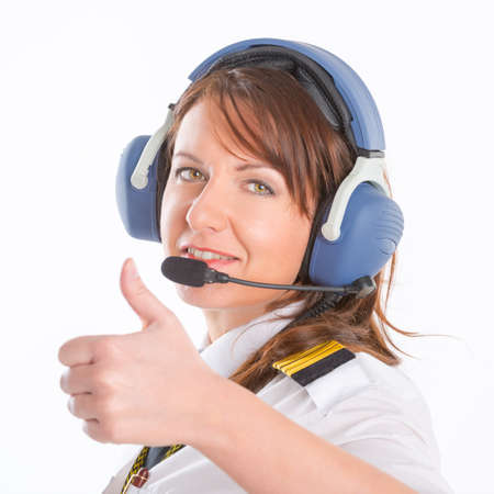 atc: Beautiful woman pilot with headset used in aircraft Stock Photo