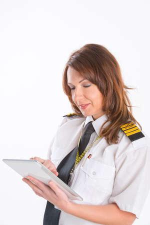 epaulettes: Beautiful woman pilot wearing uniform with epaulettes holding tablet Stock Photo