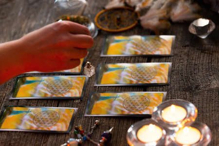 astrologist: Fortune teller holding a pendulum over tarot cards