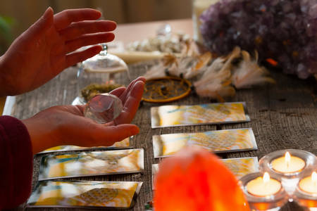 astrologist: Fortune teller holding a rhinestone over tarot cards Stock Photo
