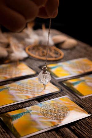 Waarzegster die een slinger boven tarotkaarten