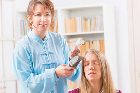 eastern health treatment: Finding an acupuncture point with electronic device which could be also used to apply lectroacupuncture, PENS Stock Photo