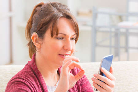 Smiling Deaf woman talking using sign language on the smartphones cam Stock Photo