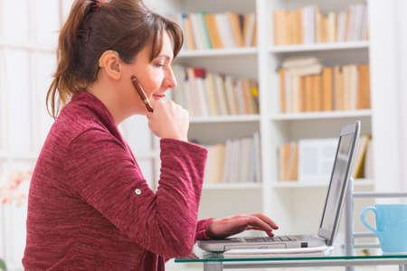 Slechthorende vrouw werken met laptop thuis of op kantoor