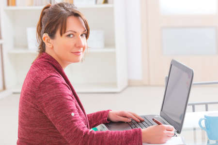 outwork: Hearing impaired woman working with laptop at home or office