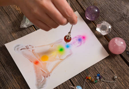 transcendence: Chakras illustrated over human body with natural crystals and pendulum Stock Photo