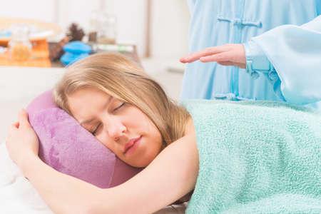 reiki: Professional Reiki healer doing reiki treatment to young woman Stock Photo