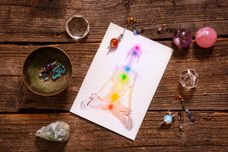 tantra: Chakras illustrated over human body with natural crystals and pendulum Stock Photo