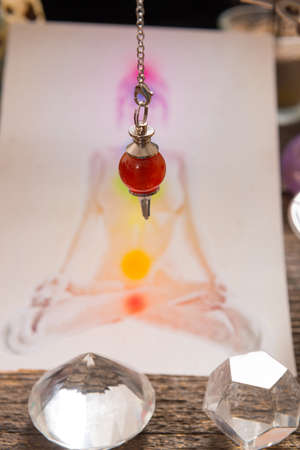 chakra energy: Chakras illustrated over human body with natural crystals and pendulum Stock Photo