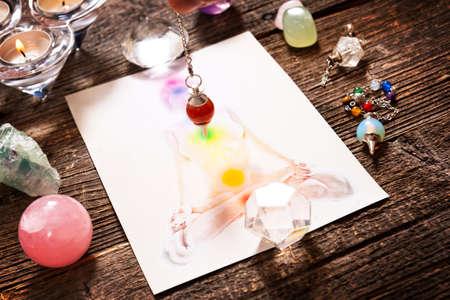Chakra's geïllustreerd meer dan menselijk lichaam met natuurlijke kristallen en slinger Stockfoto