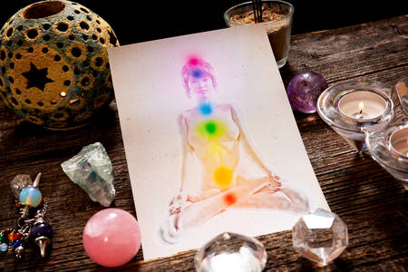 Chakras ilustran sobre el cuerpo humano con cristales naturales y péndulo Foto de archivo