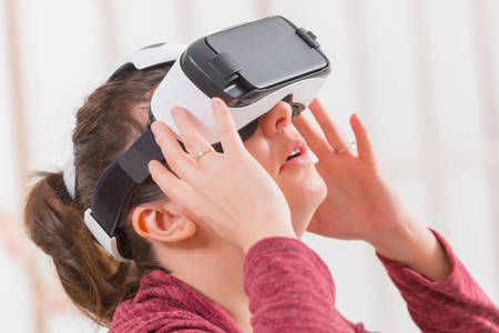 Happy woman using virtual reality headset at home Stock Photo