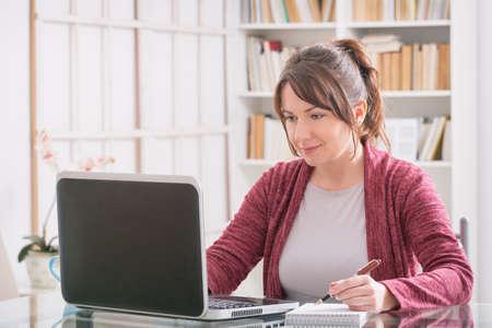 Media de edad mujer sentada a la mesa y trabajar con el ordenador portátil