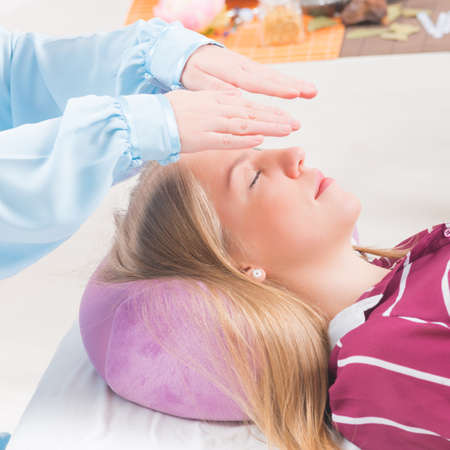 chakra energy: Professional Reiki healer doing reiki treatment to young woman Stock Photo