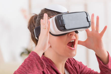 VIRTUAL REALITY: Happy woman using virtual reality headset at home Stock Photo