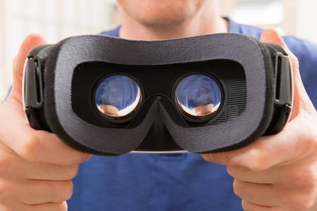 headset: Man using virtual reality headset at home Stock Photo