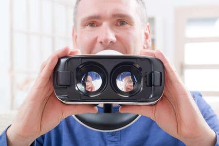 Man using virtual reality headset at home Stock Photo