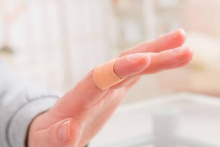 adhesive bandage: Applying adhesive bandage on bleeding finger Stock Photo