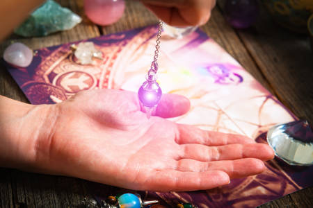 characterization: Palm reading, characterization and foretelling the future through the study of the palm with pendulum Stock Photo