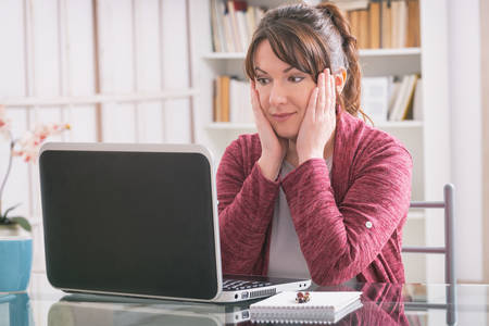 mid distance: Mid age woman sitting at table and working with laptop Stock Photo