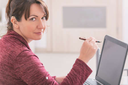 Deaf woman wearing hearing aid using laptop at home Stock Photo