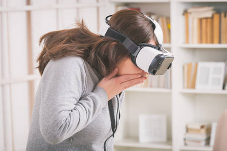 Woman using virtual reality headset to fight her phobias or fears at home