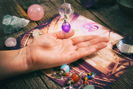 Palm reading, characterization and foretelling the future through the study of the palm with pendulum Stock Photo