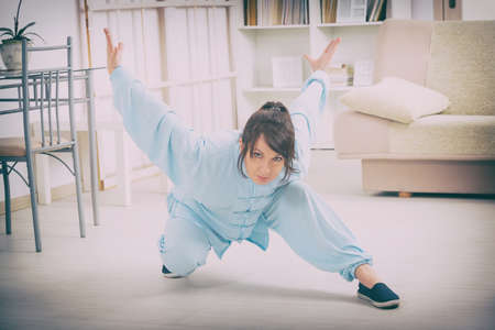 qigong: Beautiful woman doing qi gong tai chi exercise or reiki wearing professional, original Chinese clothes at home Stock Photo