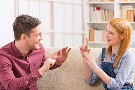 그녀의 청각 장애 남자와 기호 언어를 사용하여 얘기하는 젊은 웃는 여자 스톡 콘텐츠