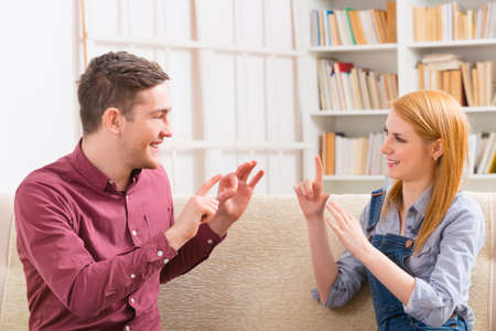impairment: Smiling young woman talking using sign language with her hearing impairment man