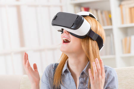 Happy woman using virtual reality headset at home Banco de Imagens