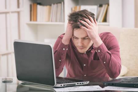 hands on head: Overworked young man sitting at the desk and holding his head Stock Photo