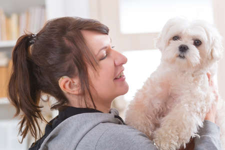 Young, smiling woman wearing deaf aid and holding her little dog Stock Photo