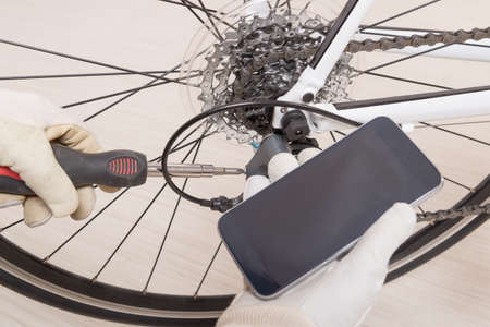 prepare: Hand with screwdriver adjusting bicycles rear derailleur and checking on-line manual on the smart phone