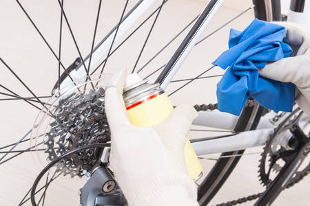 freewheel: Preparing bicycle for a new season. Hands with cloth and cleaning or lubricant spray Stock Photo