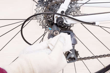 freewheel: Preparing bicycle for a new season. Hand with cloth cleaning derailleur