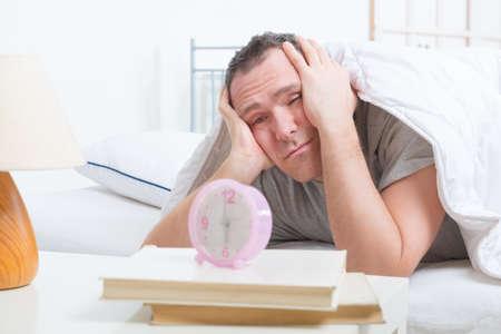 despertarse: Hora de despertar. Hombre cansado con la cabeza.