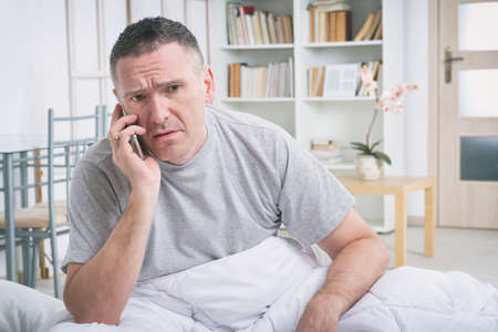 answering phone: Man answering phone in the morning Stock Photo