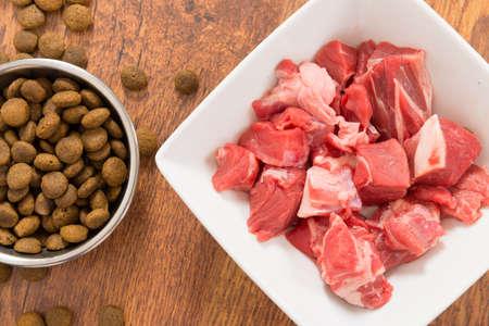 La carne en un bol como opuesto a la comida seca dog'd Foto de archivo