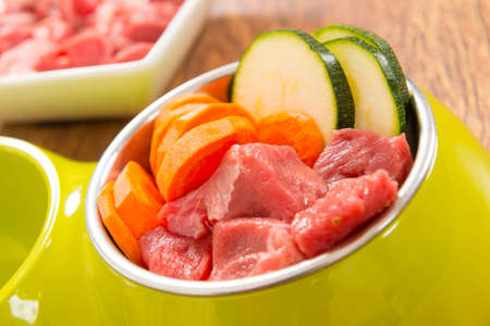 Natural, organic dogs food in a bowl with ingredients zucchini, carrot and raw meat