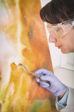 artwork painting: Artwork conservator at work with old painting wearing protective suit