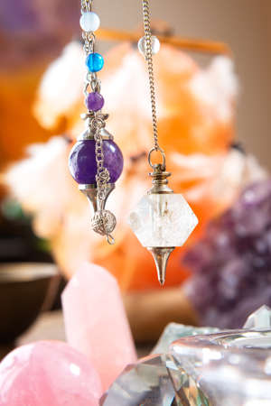 Pendulums crystal pendulum, amethyst, tool for dowsing. Crystals underneath and in background. Archivio Fotografico