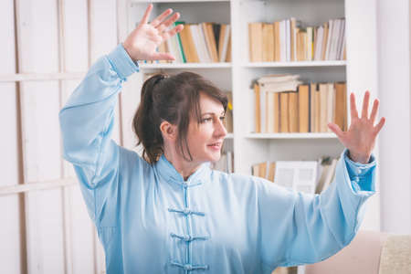 reiki: Beautiful woman doing qi gong tai chi exercise or reiki wearing professional, original Chinese clothes at home Stock Photo