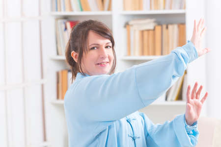 qi: Beautiful woman doing qi gong tai chi exercise or reiki wearing professional, original Chinese clothes at home Stock Photo